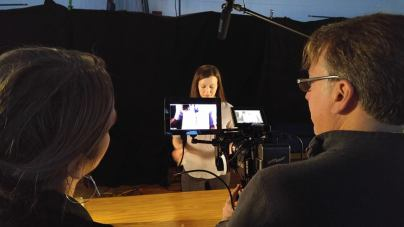 """Director of Photography Gil Whitney and Director Steph Greegor discuss lighting as they film actress Dianna Craig on te set of """"Magic"""" for Water for Good public service announcement."""