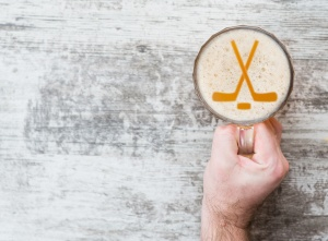 man's hand holds a beer mug with hockey symbols on foam  - sticks and puck. Top view. Space for text